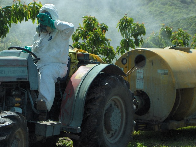Worker with full body protection on a tractor.