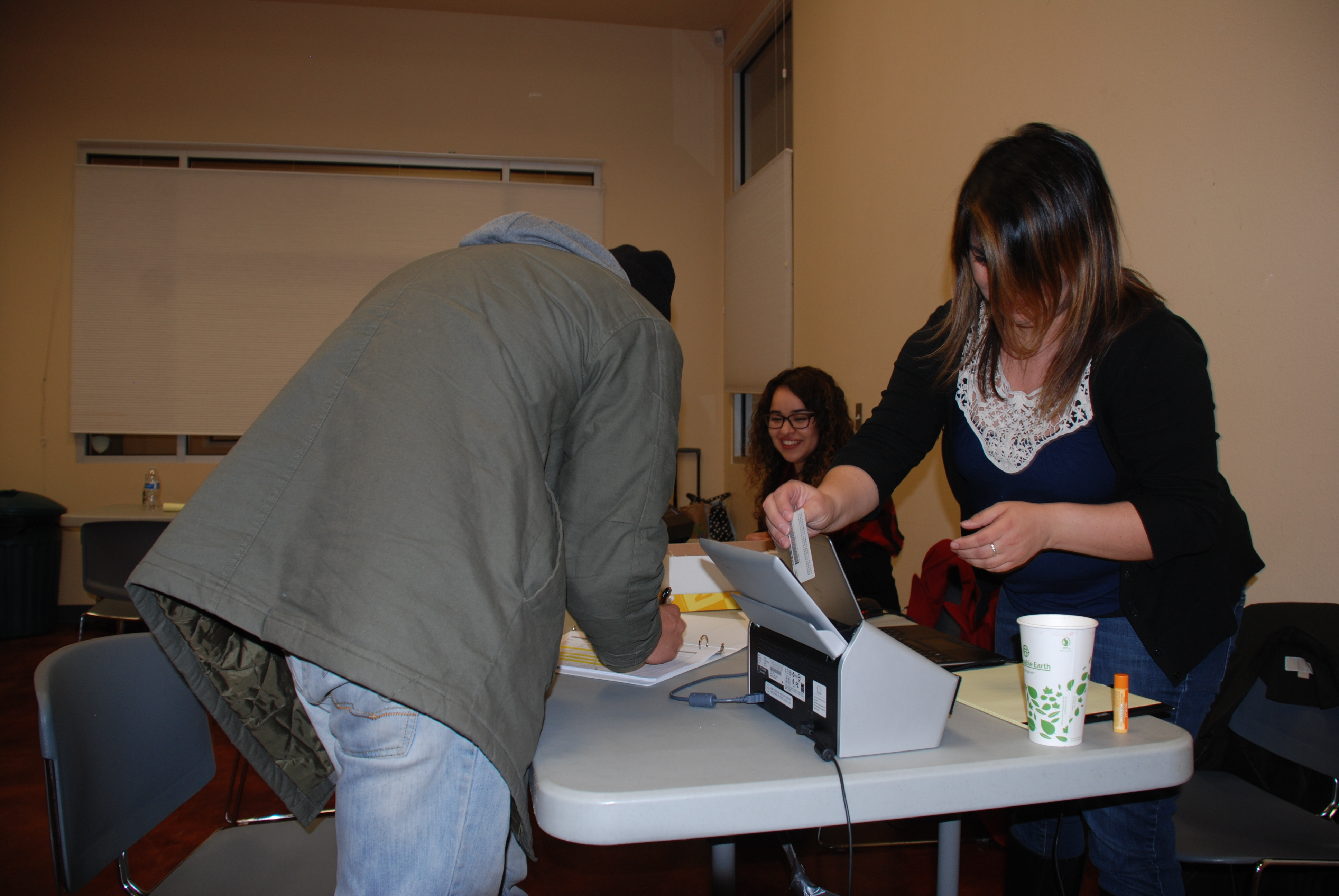 Legal Assistants, Cheli Bueno and Elvia Bueno, helping distribute settlement checks.